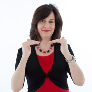 Image of Jane Cordell wearing a red dress and a black jacket.